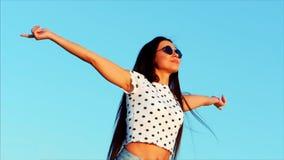 自由的美丽的愉快的微笑的快乐的时髦的欧洲甜女孩,举他的手高在美丽的蓝色 股票录像