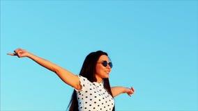 自由的美丽的愉快的微笑的快乐的时髦的欧洲甜女孩,举他的手高在美丽的蓝色 股票视频