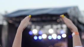 自由的露天节日全部在自由摇滚乐音乐会的爱好者在露天,爱好者的手在欢乐的音乐鼓掌了,延迟 影视素材