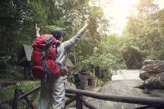 自由站立与背包和享用的旅客人 库存图片
