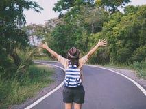 自由站立与被举的胳膊和享受美好的自然的旅客妇女 图库摄影