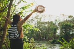 自由站立与被举的胳膊和享受美好的自然的旅客妇女 免版税库存照片