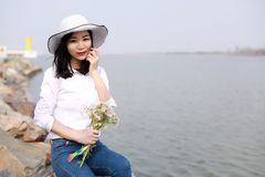 自由粗心大意的causual秀丽在湖海洋河海滩举行旁边享受好时间每花帽子坐岩石的穿戴 免版税库存照片