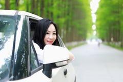 自由粗心大意的causual秀丽坐在森林公路的白色汽车停车处在室外夏天的自然 免版税库存照片