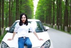 自由粗心大意的causual秀丽坐在森林公路的白色汽车停车处在室外夏天的自然 库存照片