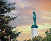 自由纪念碑里加 拿着象征拉脱维亚的三个地区的三个金星的妇女 库存图片