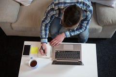 自由职业者人运作的在家工作,做在notebok的笔记 库存照片