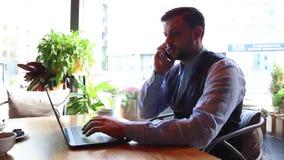 自由职业者商人研究在咖啡馆的膝上型计算机和谈话在电话, 股票视频