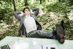 自由职业者放松了在绿色森林企业概念的办公室桌上 库存照片