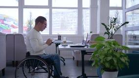 自由职业者的事务,在轮椅戴着眼镜致残的老人使用一个手机和工作在膝上型计算机坐 影视素材