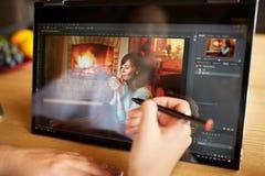 自由职业者研究有照片的敞篷车便携式计算机编辑软件的retoucher妇女使用铁笔 摄影师 免版税库存图片
