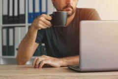 自由职业者饮用的咖啡和看膝上型计算机屏幕 免版税库存照片