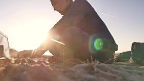 自由职业者 供以人员在膝上型计算机自由职业者的运作的剪影坐沙子日落太阳强光太阳 股票视频