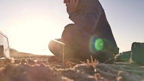 自由职业者 供以人员工作在膝上型计算机自由职业者坐沙子日落太阳强光太阳剪影 影视素材