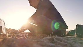 自由职业者 供以人员运作在膝上型计算机自由职业者的剪影坐沙子日落太阳强光太阳 影视素材