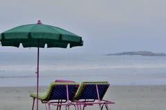 自由自在:在风景海滩的伞和海滩床 库存图片
