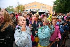 自由街道音乐会喝彩声鼓掌,高兴并且跳舞普遍的星、成人和儿童听众的爱好者 免版税库存图片