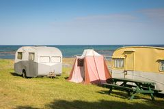 自由野营在有蓬卡车的和帐篷在东海岸靠岸,吉斯伯恩,北岛,新西兰 免版税库存图片