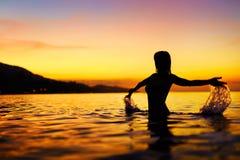 自由,享受 妇女在日落的海运 幸福,健康L 免版税库存照片