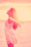 自由-享受日落的自由的愉快的平静的妇女 免版税库存图片