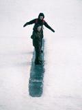 自立被定调子的图象的母亲以乘坐的孩子在冰小山 免版税库存照片
