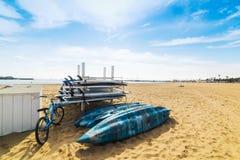 自行车、皮船和冲浪板在沙子 库存照片