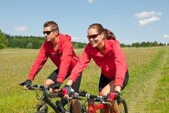 自行车乘坐嬉戏夏天的夫妇草甸 图库摄影