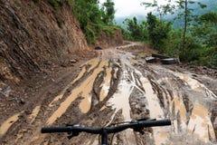 自行车乘驾通过泥泞的土路 库存图片