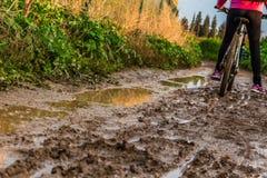 自行车乘驾通过泥泞的土路 免版税库存照片