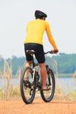 年轻自行车人佩带的车手衣服和安全恶劣环境测井背面图  免版税库存照片