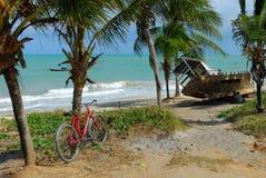 自行车和小船在一个热带海滩 免版税图库摄影