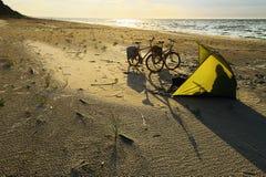 自行车和帐篷在空的海滩在波儿地克的海边,由后照由日落 图库摄影