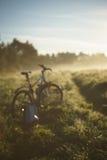 自行车和背包在有雾的早晨之前 库存图片