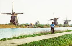 自行车和风车的人在小孩堤防,荷兰 免版税库存照片