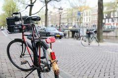 自行车在前景的街道上停放了与阿姆斯特丹,荷兰典型的运河和建筑学  免版税库存图片