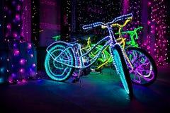 自行车在圣诞节庆祝照明设备夜背景城市 图库摄影