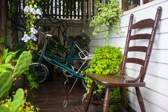 自行车在有木椅子的庭院里 库存图片