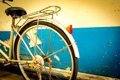 自行车在老白色和蓝色削皮油漆混凝土墙旁边停放了 库存图片