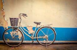 自行车在老白色和蓝色削皮油漆混凝土墙旁边停放了 免版税库存照片