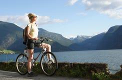 自行车在行程妇女的湖山 免版税库存图片