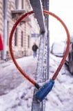 自行车垂悬在篱芭的缆绳锁在霜期间,报道用冰 免版税库存照片