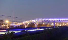 自行车天桥和通过火车在晚上 库存照片