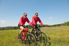 自行车夫妇草甸嬉戏夏天年轻人 免版税库存照片