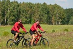 自行车夫妇草甸嬉戏春天年轻人 免版税库存照片