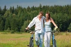 自行车夫妇草甸浪漫夏天 库存照片