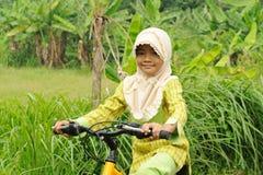 自行车女孩回教骑马 免版税库存照片