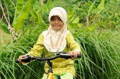 自行车女孩回教骑马 免版税图库摄影