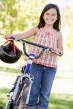 自行车女孩户外微笑的年轻人 免版税库存图片
