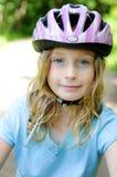自行车女孩helemt佩带 免版税库存照片