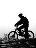 自行车山竟赛者剪影 免版税图库摄影